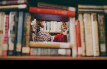 View of couple through a book shelf